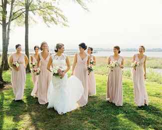 Bridesmaids walking in blush gowns with bride