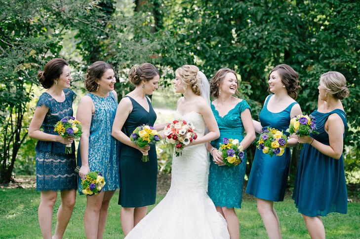 Bridesmaids were dressed in different shades of blue, meant to compliment the peacock accented floral arrangements. Each dress was different in color, style and length.