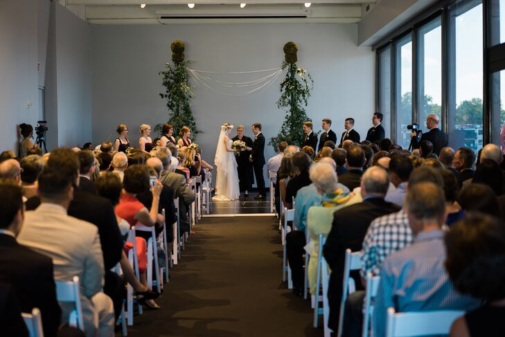 Tessa and Brendan exchanged vows in the Garden Terrace room of the Walker Art Center in Minneapolis, Minnesota. They loved the oversize windows overlooking the terrace and the sculpture garden. With gorgeous vistas and a short ceremony, the couple kept their ceremony decor minimal. Martha's Gardens created the small trellis wedding arbor, including potted trees, smilax vines and ribbons.