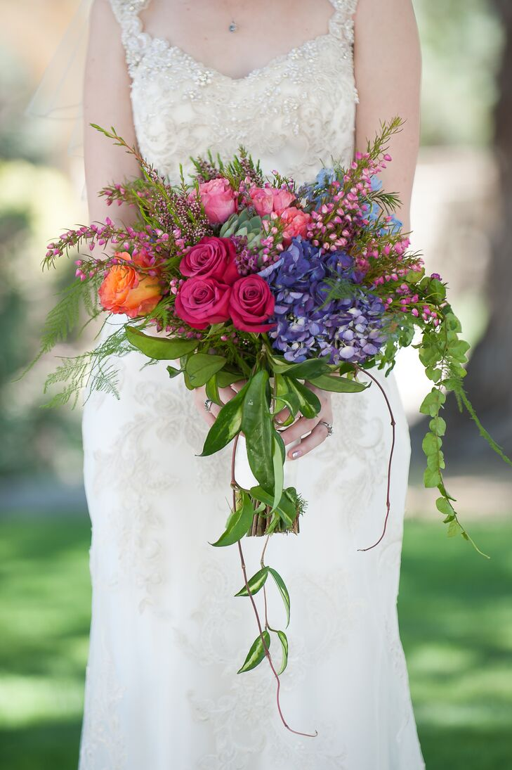 "Greenleaf Wholesale Florists created Christine's stunning cascading bouquet full of vibrant flowers, including roses in hot pink, light pink and orange, wax flowers, purple and blue hydrangeas, succulents and leafy greens. ""I wanted flowers that would mimic the color of the mosaic,"" the bride says."