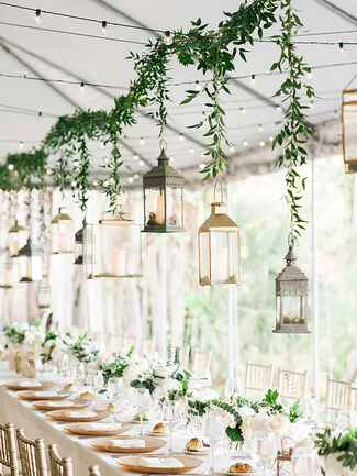 Tented wedding reception with hanging lanterns and greenery