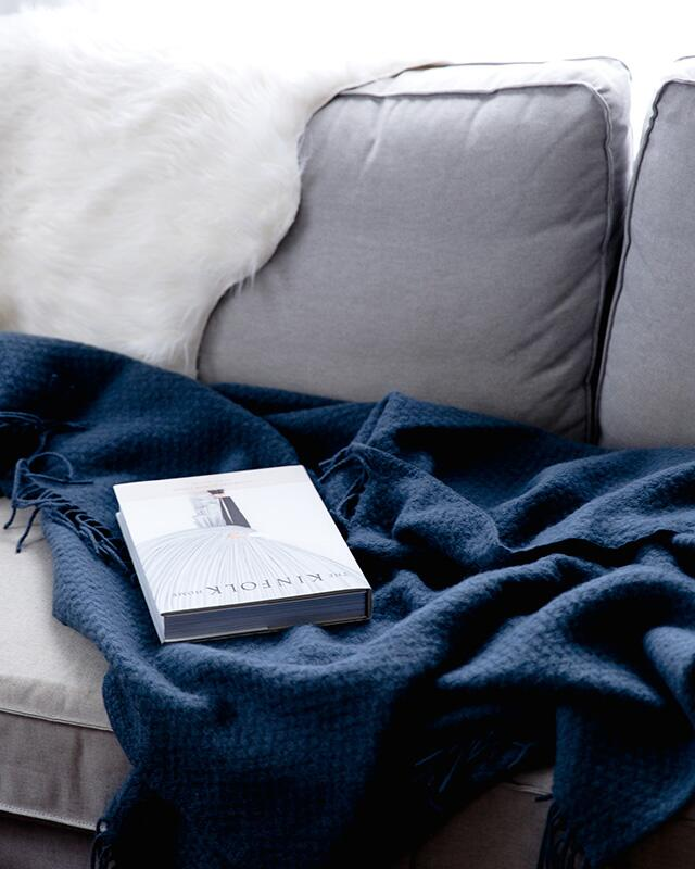 grey couch with blue blanket