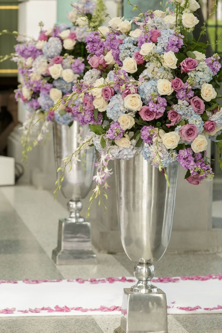 Two grand arrangements of ivory roses, pink roses and light blue hydrangeas were set in large silver trumpet vases at the end of  Deirdre & Damian's ceremony aisle.