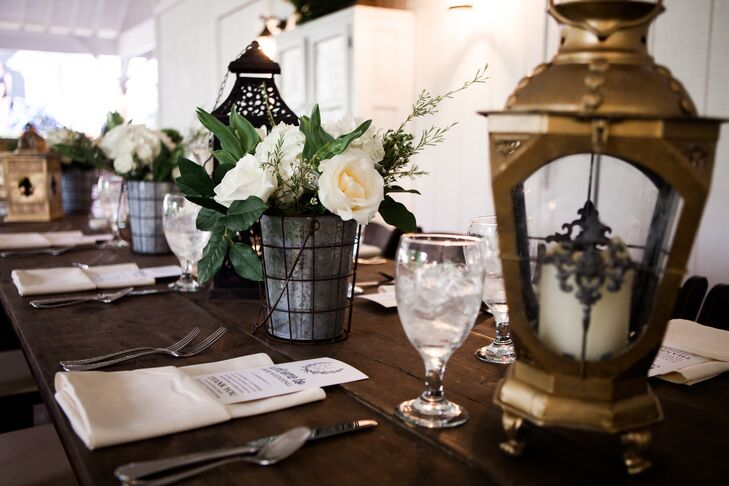 Lanterns, galvanized pails and floral arrangements in a palette of white and ivory decorated the tables.