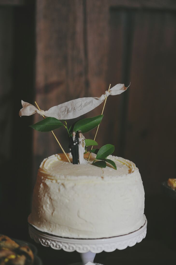 "The groom's aunt made a strawberry cream cake for the couple's wedding reception. ""The cake topper belonged to Phil's great grandparents,"" Brittany says. ""Our friend who runs Ink & Ivory stationary mad the little banner on top."""