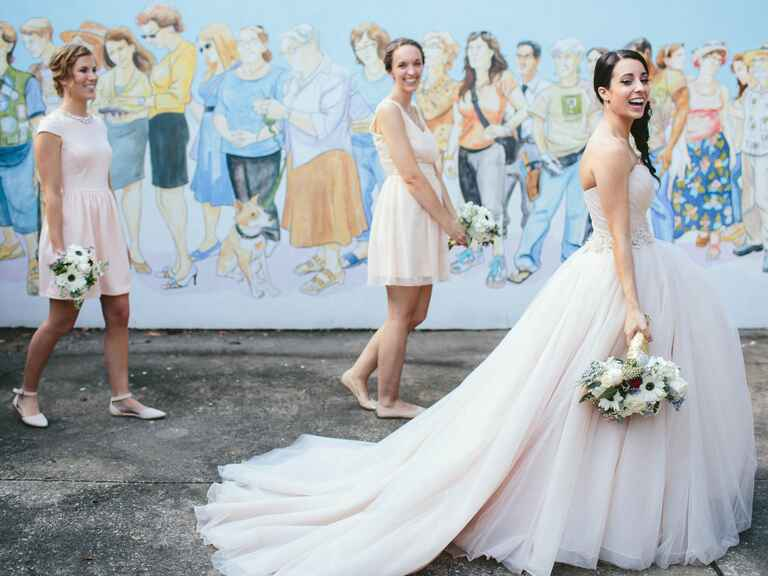 Bride walking with bridesmaids next to mural