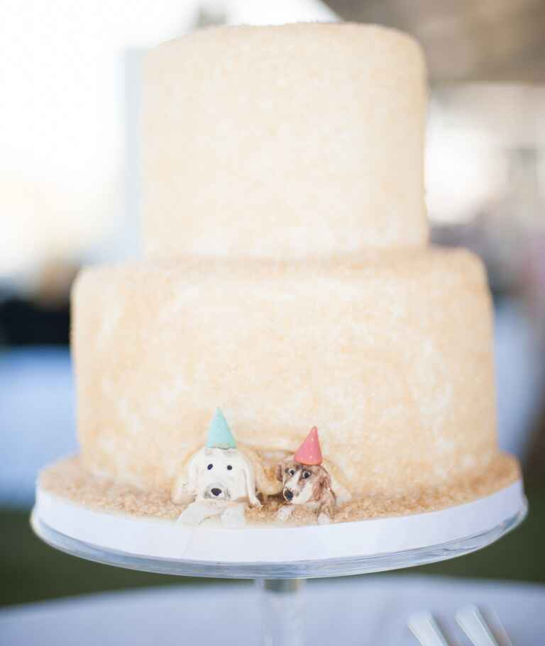 Two dogs peeking out from under a two-tier wedding cake