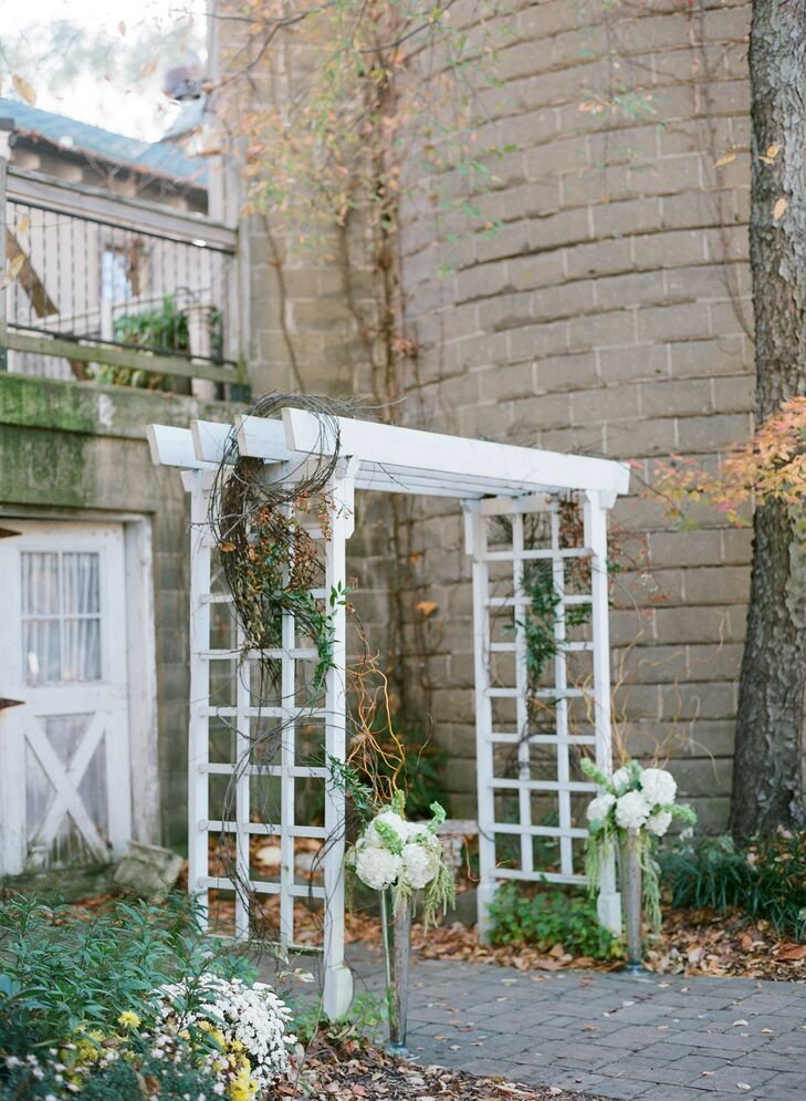"The couple kept the overall look of the ceremony simple, adding only willow branches and white hydrangeas to the white arbor. ""We were blessed with the most beautiful October day and let nature do her work with regards to decor,"" says Christiana."
