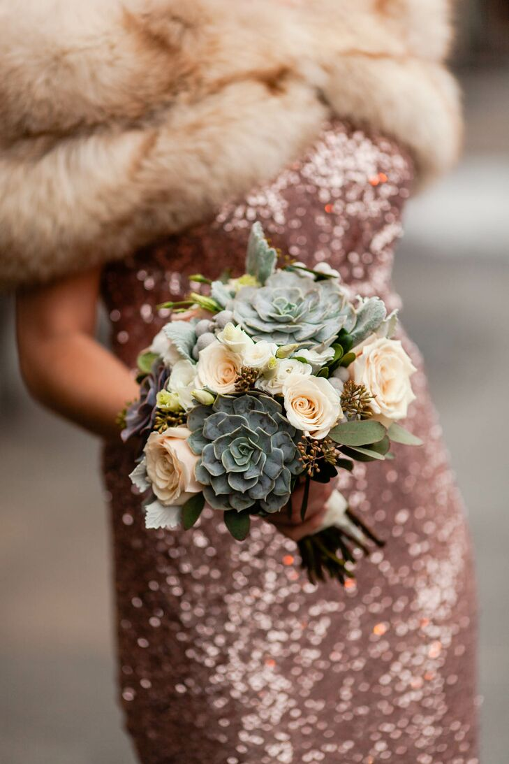 Beth and David's winter wedding called for something a little different when it came to the florals, with many classic varieties being out of season. For Beth's bouquet, Opalia Flowers put together a stunning arrangement of succulents, brunia berries, dusty miller, seeded eucalyptus and a few blush roses that fused modern and classic styles, while playing up the winter season.