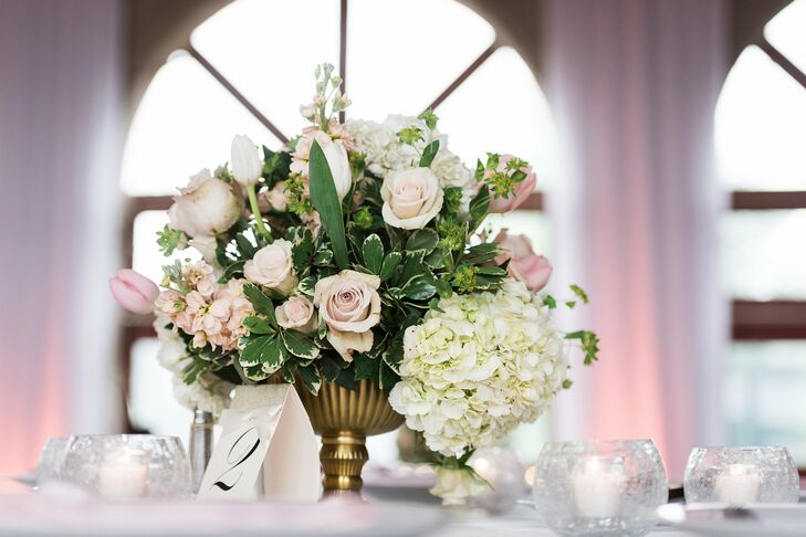 The reception tables were decorated with classic gold vases filled with garden-inspired arrangements including blush roses, blush sweet peas, pink tulips and white hydrangeas along with greenery. The centerpieces were accented with small votives candle for some added romance.
