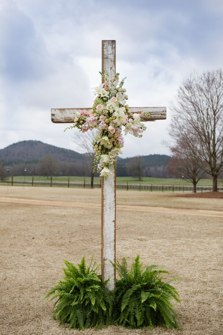 """We wanted the focus to be on family and our faith,"" Mary Caroline says. The King's Garden helped to emphasize this with a sweet accent along the altar space. Pink garden roses, white stargazer lilies and white and pink delphiniums topped the wooden cross as greenery circled its base."