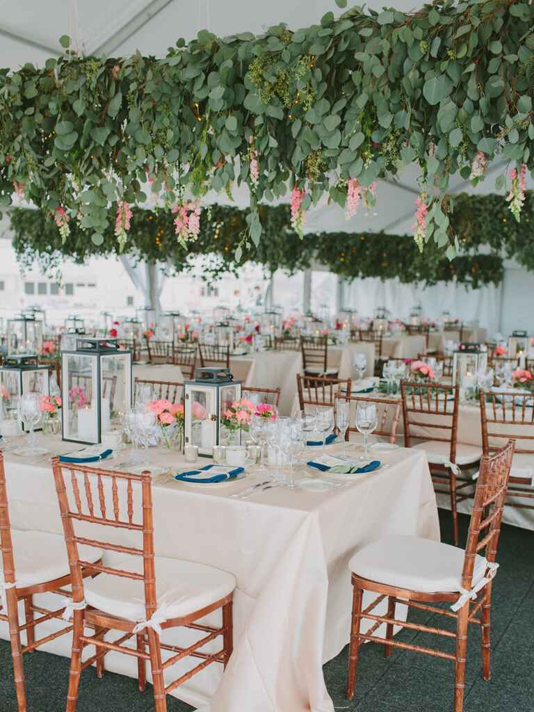 Whimsical outdoor wedding tent with hanging silver dollar eucalyptus