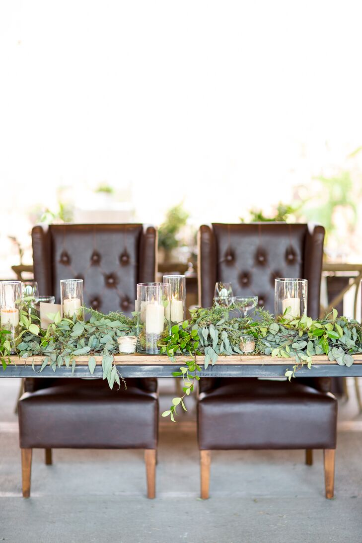 Faith and Brent's rustic wooden sweetheart table was covered in overflowing greenery and candles. They sat in regal yet comfortable brown armchairs facing their guests.