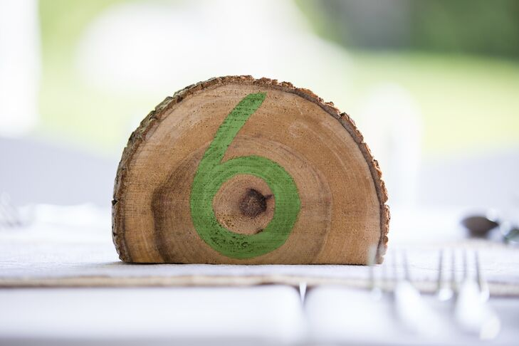 Green painted tree slices were used for table numbers, adding to the rustic, natural look of the wedding.