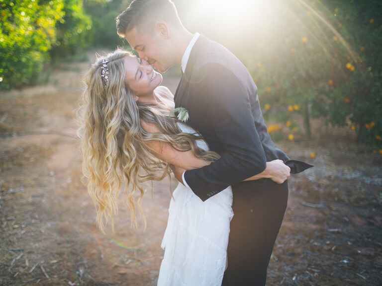 Bride and groom hugging in lemon grove