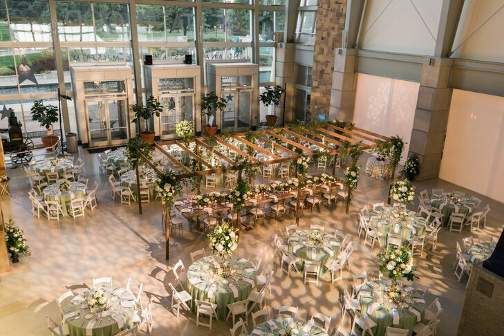 White and green florals, round tables, glamorous chandeliers, a custom pergola and farm tables created an indoor garden party vibe at Indiana State Museum in Indianapolis, Indiana.