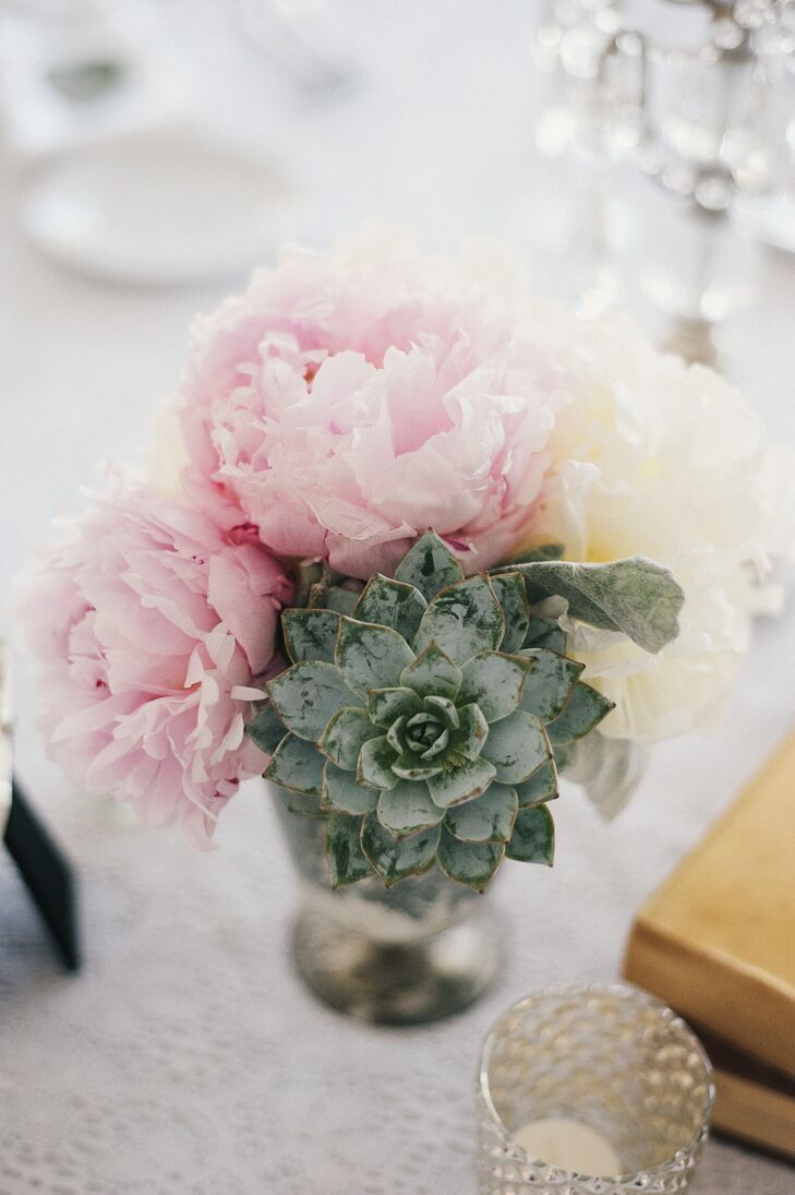 Pink and white peonies, succulents, and dusty miller filled small silver vases at the reception.