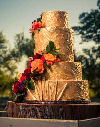 Metallic gold wedding cake with gold leaves and jewel tone floral cascade