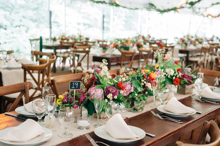 To allow the vibrancy of the centerpieces to shine through without betraying the feeling of simple elegance they were after, Olivia and Ben rounded out the decor with wooden farm tables, natural-colored linens, classic white dinnerware and French country chairs.