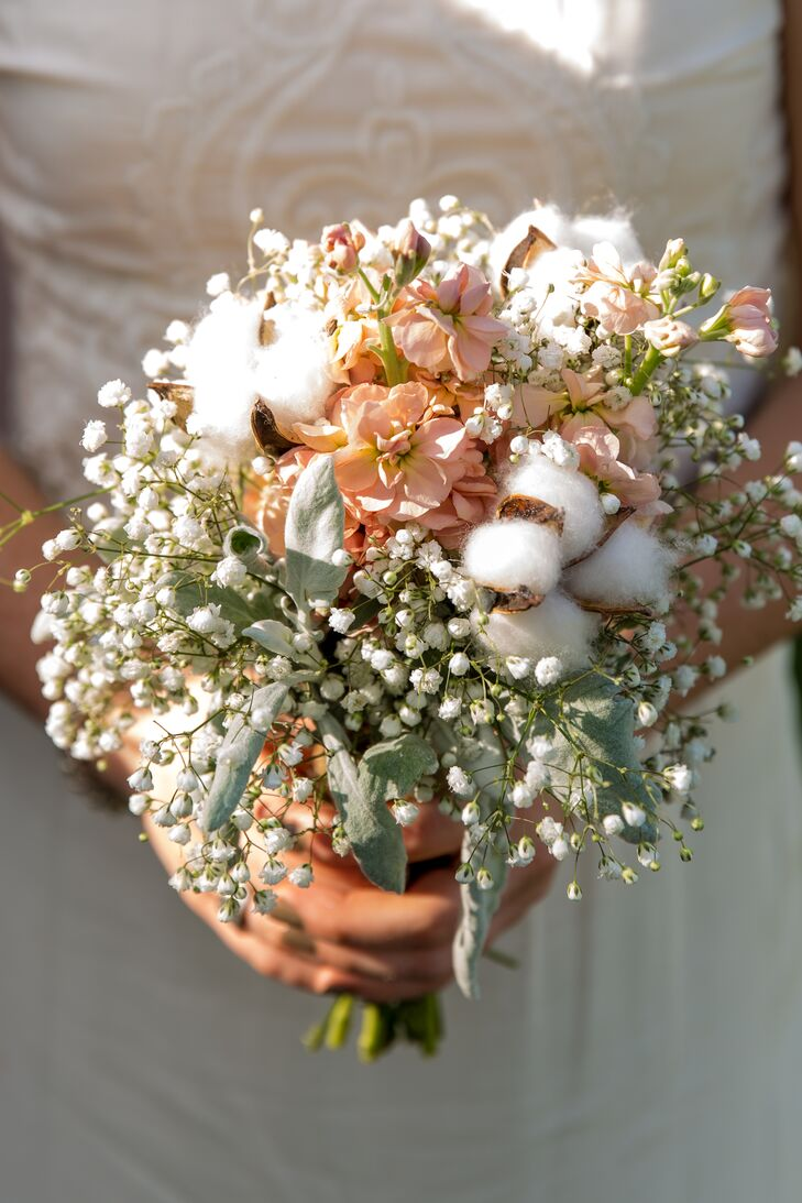 The bridesmaids carried small bouquets, including stock, baby's breath, dusty miller and balls of cotton. Since Fresh Flower Market arranged all the flowers, the bridesmaid bouquets echoed Leslie's bouquet for a cohesive, rustic look.