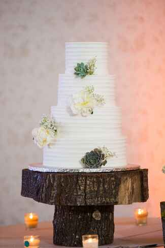 White textured four tiered wedding cake with cream flowers and succulents