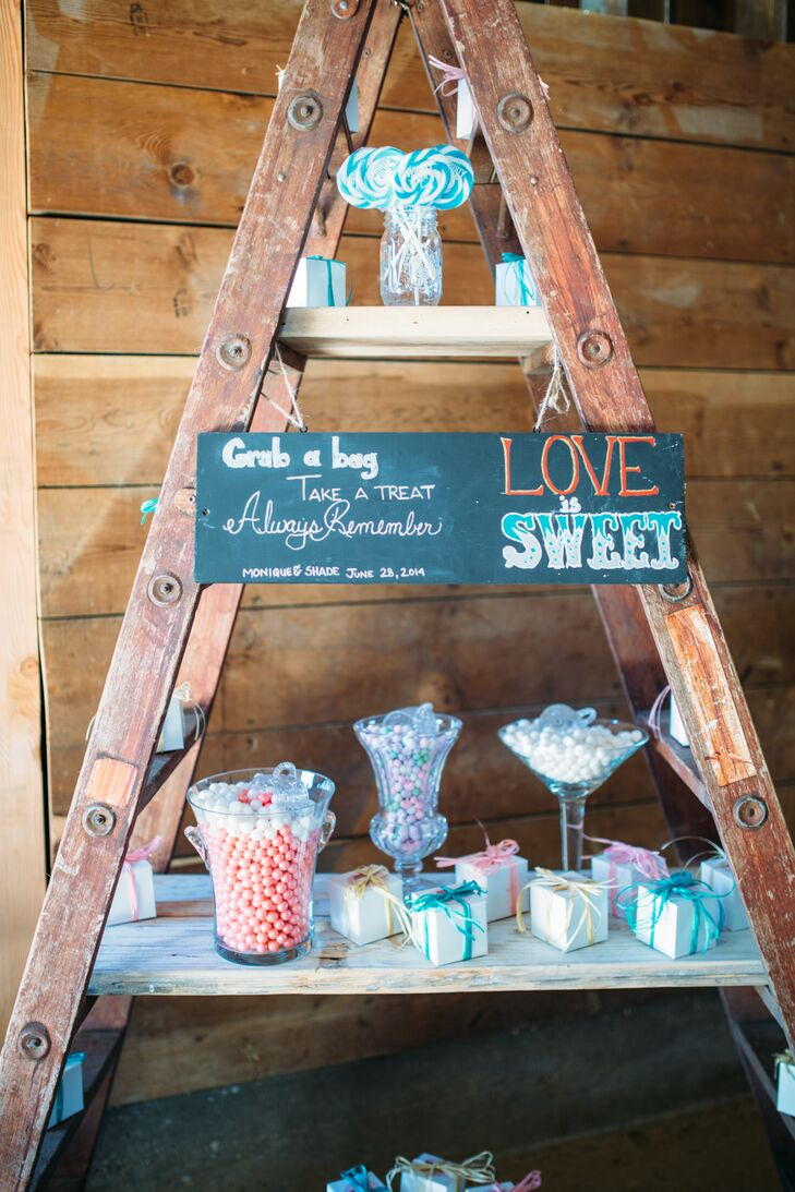 "During the reception, guests wandered into the barn to pick out sweets and treats from the ""candy store"" display. They picked from a range of candy and cupcakes boxed in colorful packaging, with a chalkboard sign that read ""Love Is Sweet."""