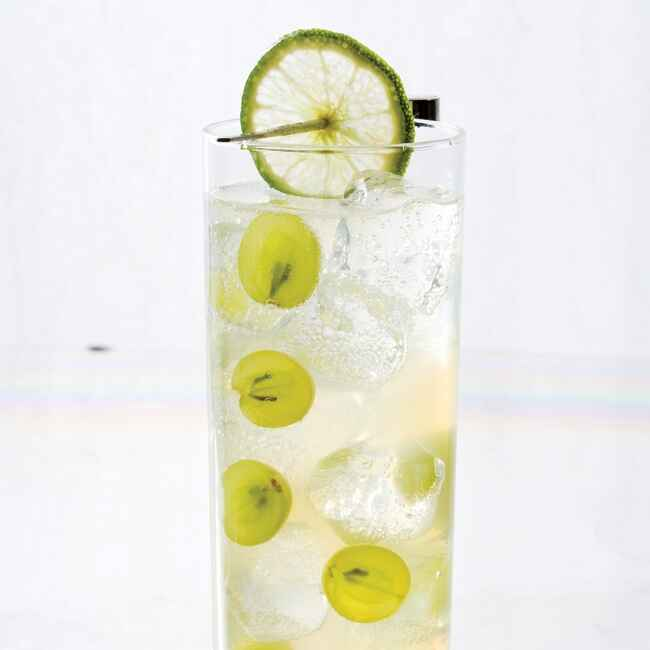 clear fizzy cocktail with sliced grapes and lime