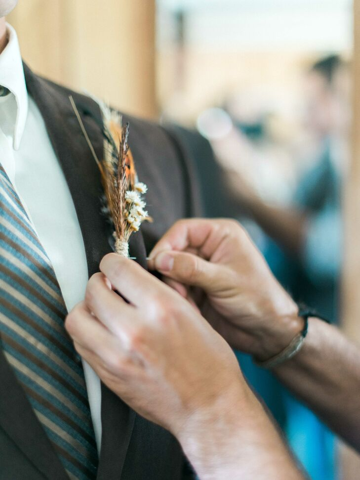 Ashley used feathers and natural grains to craft the eye-catching boutonnieres for the men. Their rustic look and neutral color scheme looked flawless with the groom and groomsmen's boots and jeans and was a perfect addition to the farm wedding.