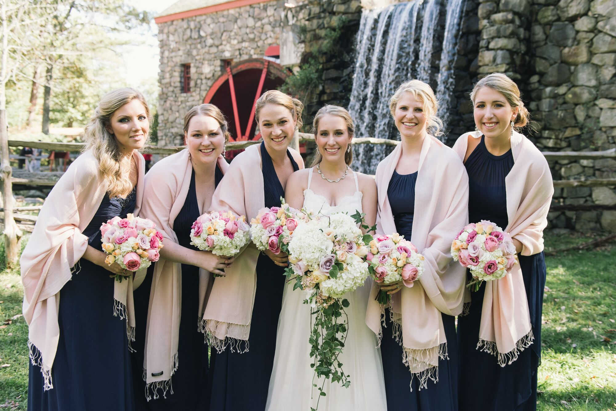 bridesmaids in long navy dresses and pink pashmina scarves