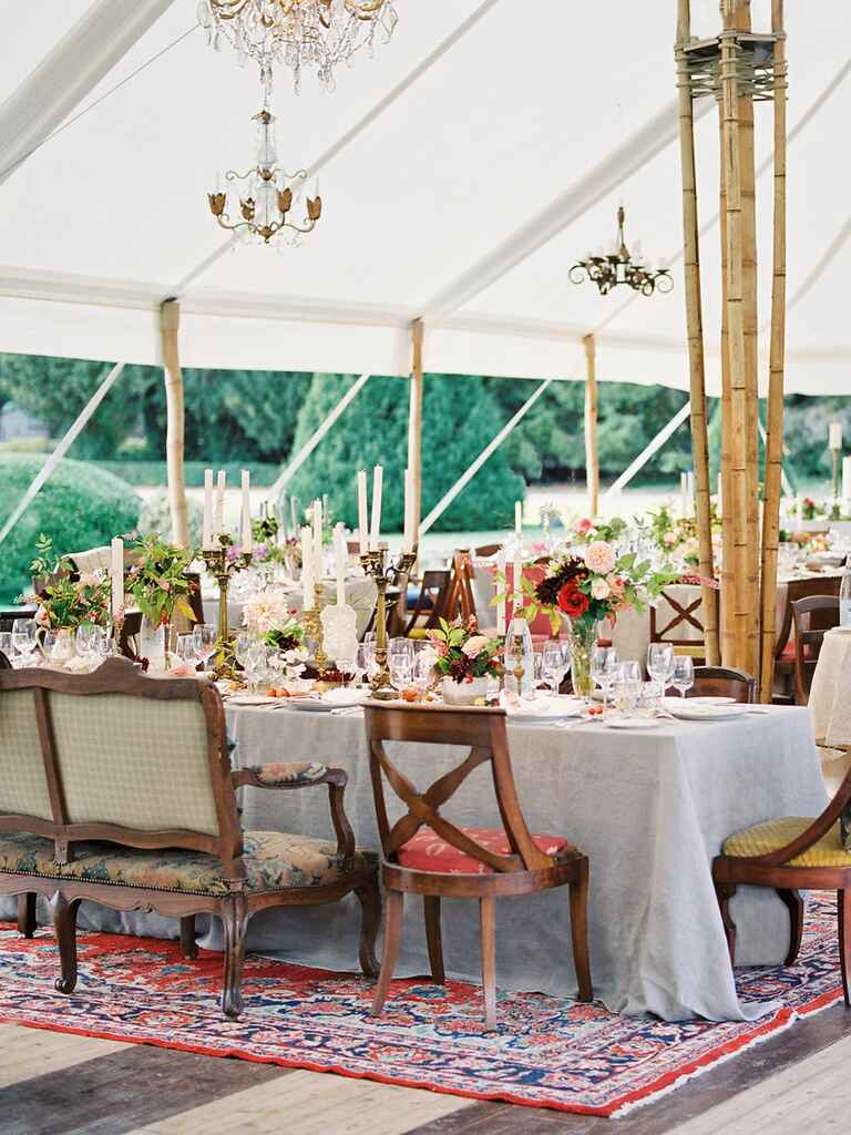 Outdoor wedding tent with mismatched chairs and rugs