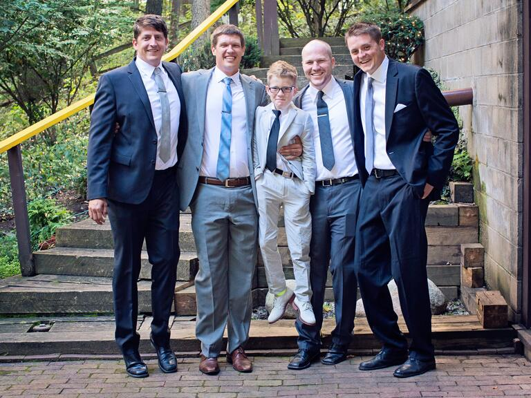 Groomsmen holding the ring bearer