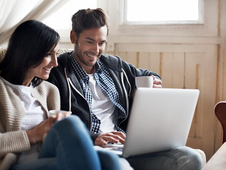 Couple looking at budget on computer