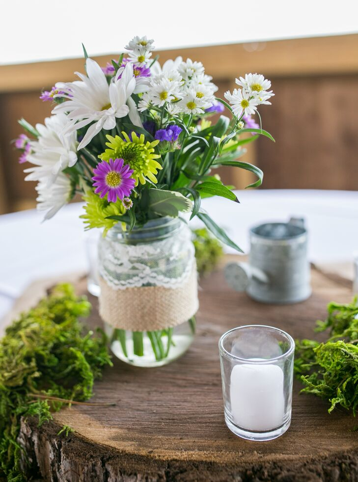 Centerpieces included daisy flower bouquets in mason jars surrounded by votive candles and natural moss.