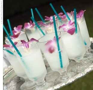 white cocktail garnished with purple orchids