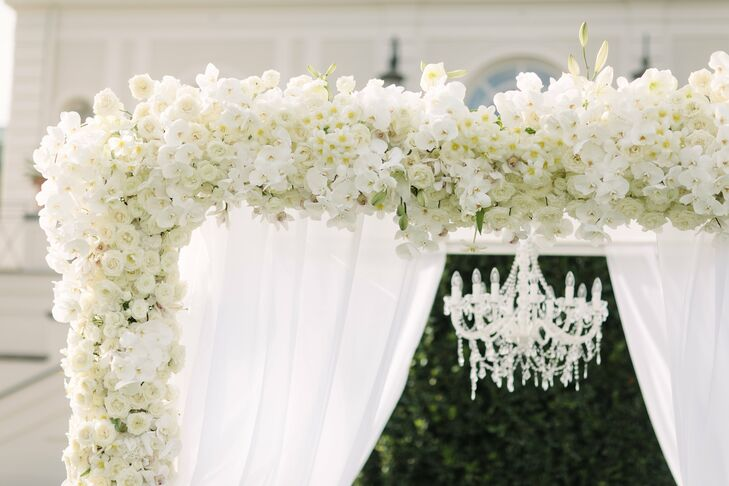 The couple shared a first kiss under a white flower arch made from bunches of fresh orchids and roses.