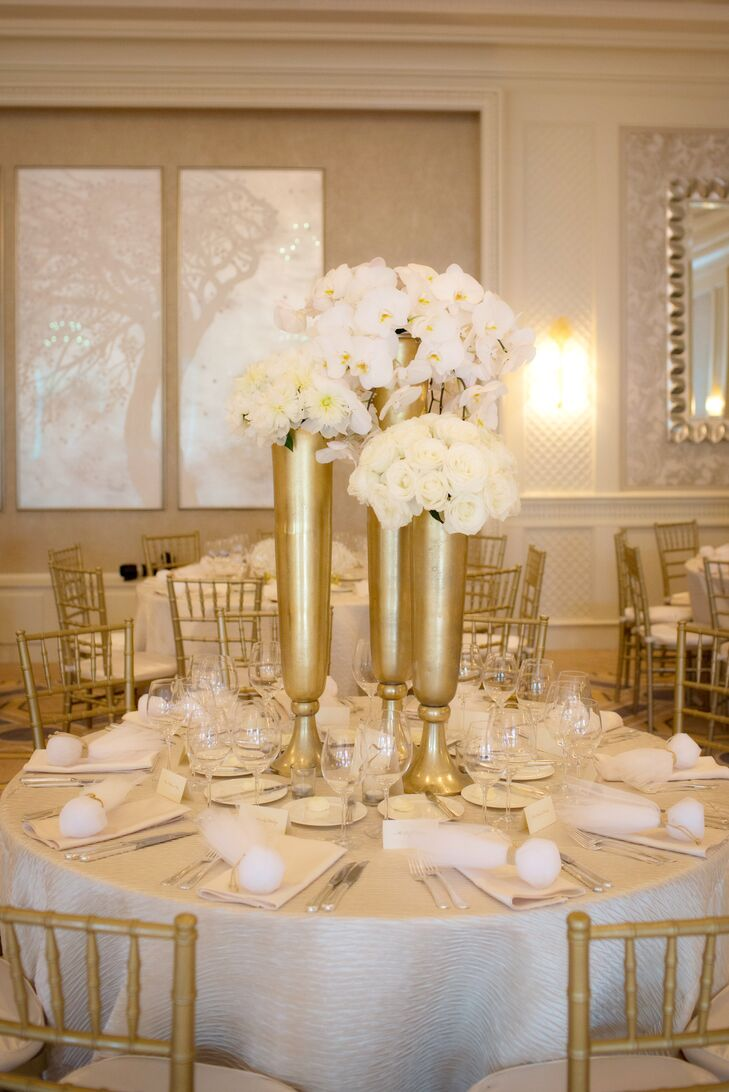 White Floral Centerpieces In Tall Gold Vases
