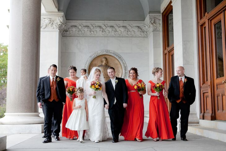 The bridesmaids worse floor-length dresses by Allure Bridals in a vibrant shade of burnt orange.