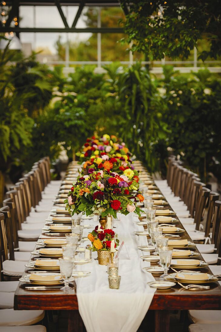 Long, dark wooden farm tables were set with elegant ivory table runners, gold china and bright floral arrangements for a timeless, sophisticated look.