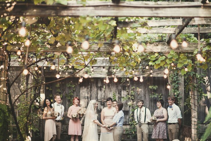Kat And Meredith Exchanged Vows Under A Huge Trellis Covered In Grape Vines Bistro Lights