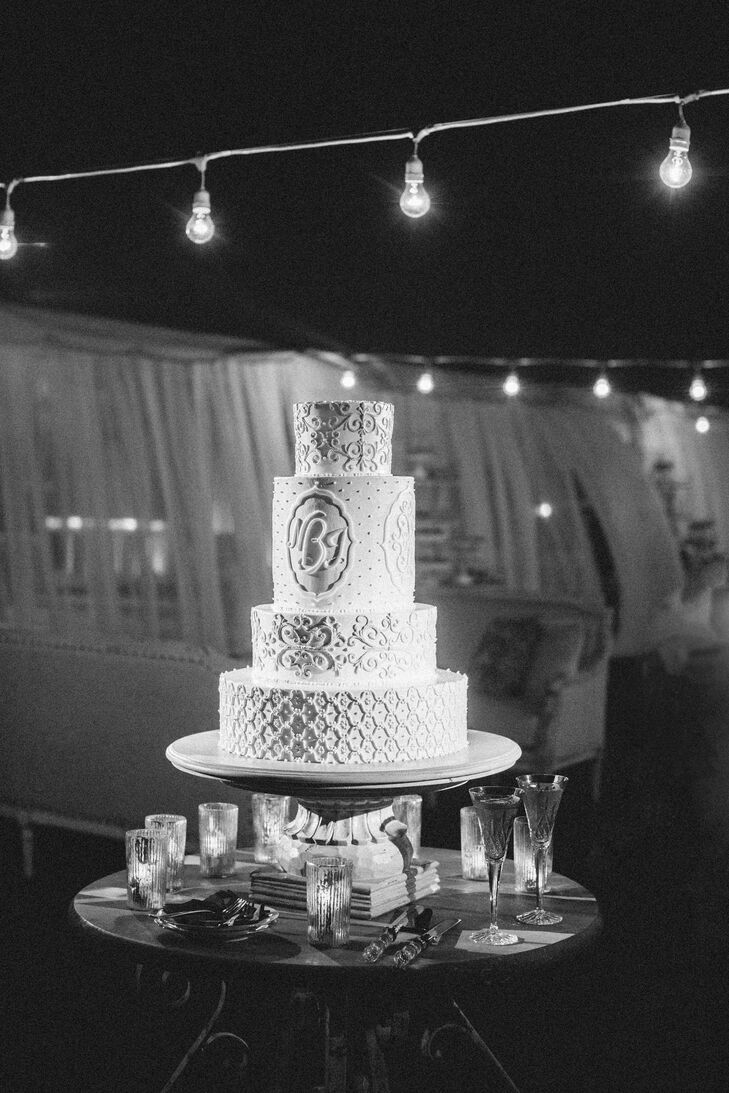 """Our wedding cake was created by the amazingly talented Jim Smeal,"" Nicole says. ""We met with him in the winter for a tasting and creative session to come up with the look we wanted. The cake was four tiers and our monogram was on all sides of one of the tiers. It was primarily white with light blue accents and sat on a custom made stand painted and distressed to go along with our vintage blue décor scheme.  The cake flavors were almond amaretto and butter cake with buttercream."""