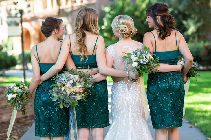 The bridesmaids wore strapless, knee-length dresses in a dark teal color, which went along with the overall wedding color palette of greens, gold and blush tones.