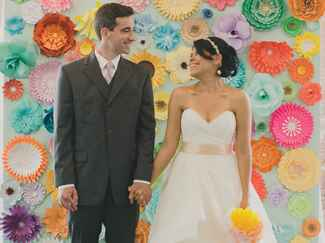 Vibrant paper flower wall at ceremony.