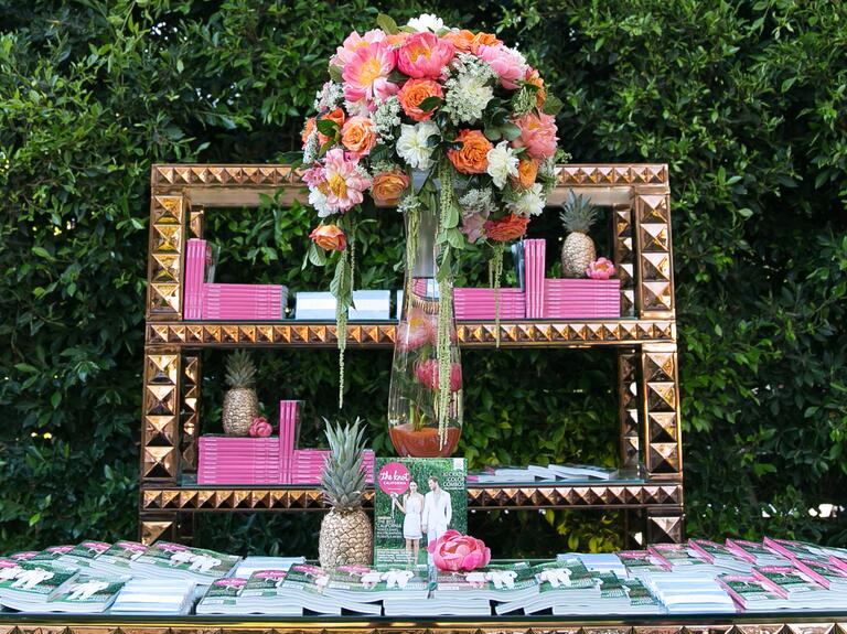 Tall flower centerpiece and gold geometric bookcase