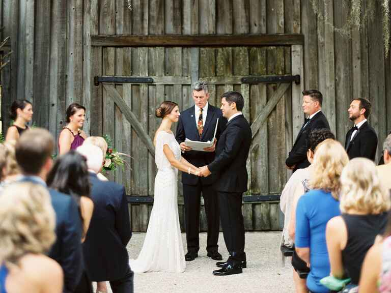 Rustic utdoor wedding ceremony in front of wooden barn doors