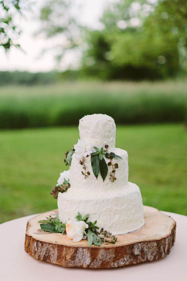 The three-tier white wedding cake had beautiful accents of leafy greens and blooms on the sides and bottom. The entire dessert sat on top of a wooden slab, embodying the natural surrounding environment.