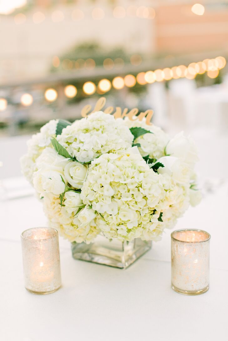 "The reception tables were decorated with white roses and hydrangeas in modern, square glass vases. ""We ate dinner on the second floor patio of the Grove, and I wanted the look to be very clean and not take away from the park surrounding the Grove as well as the beautiful view of the Houston skyline,"" Chelsea says. Metallic mercury glass candles and gold table numbers added plenty of glamour to the otherwise-neutral decor."