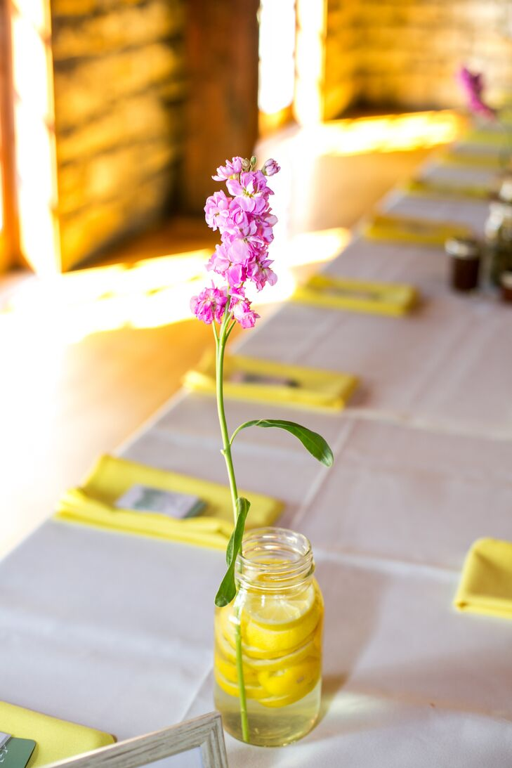 The reception tables were topped with mason jars filled with fresh lemons for a fresh, summery feel. Pink delphiniums added a pop of color to the otherwise yellow palette.