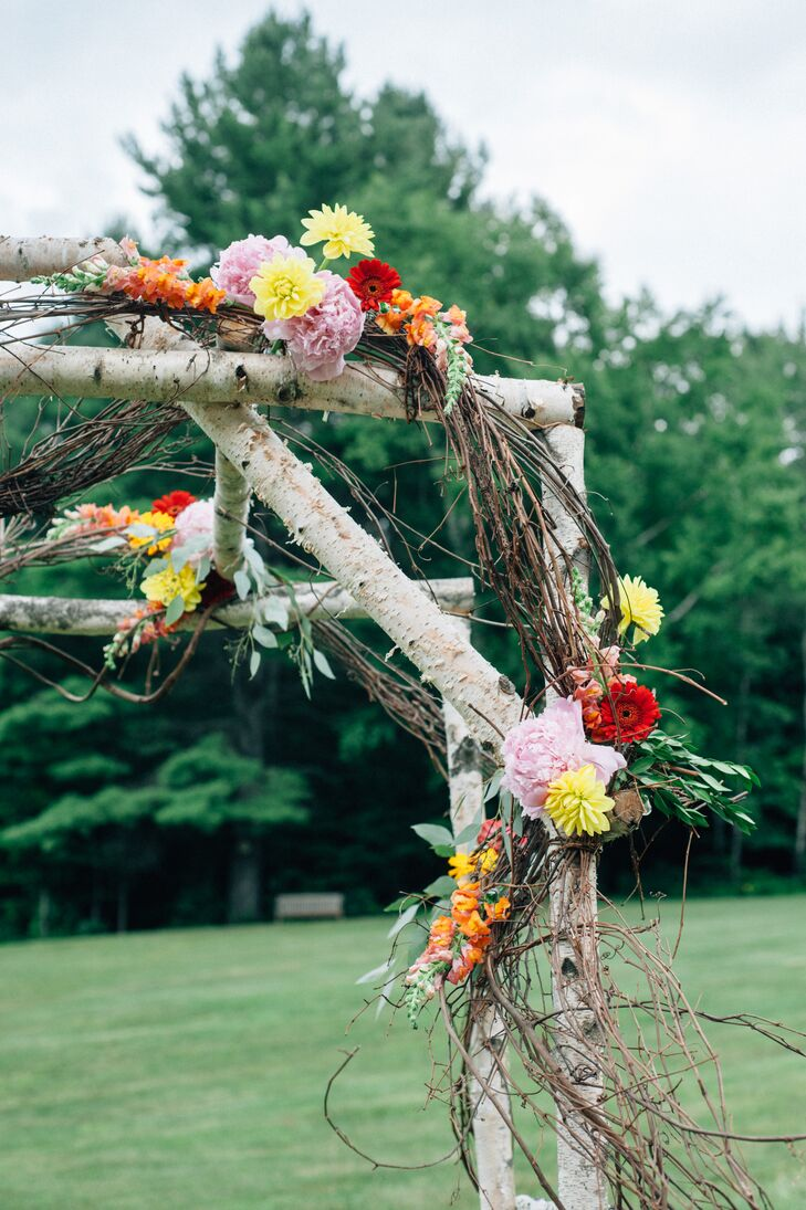 To infuse the rustic birch arch with cheery, summertime vibes, Holly Long of Naturally Elegant Designs punctuated the structure with whimsical curly willow and bouquets of fresh orange, pink and yellow flowers.