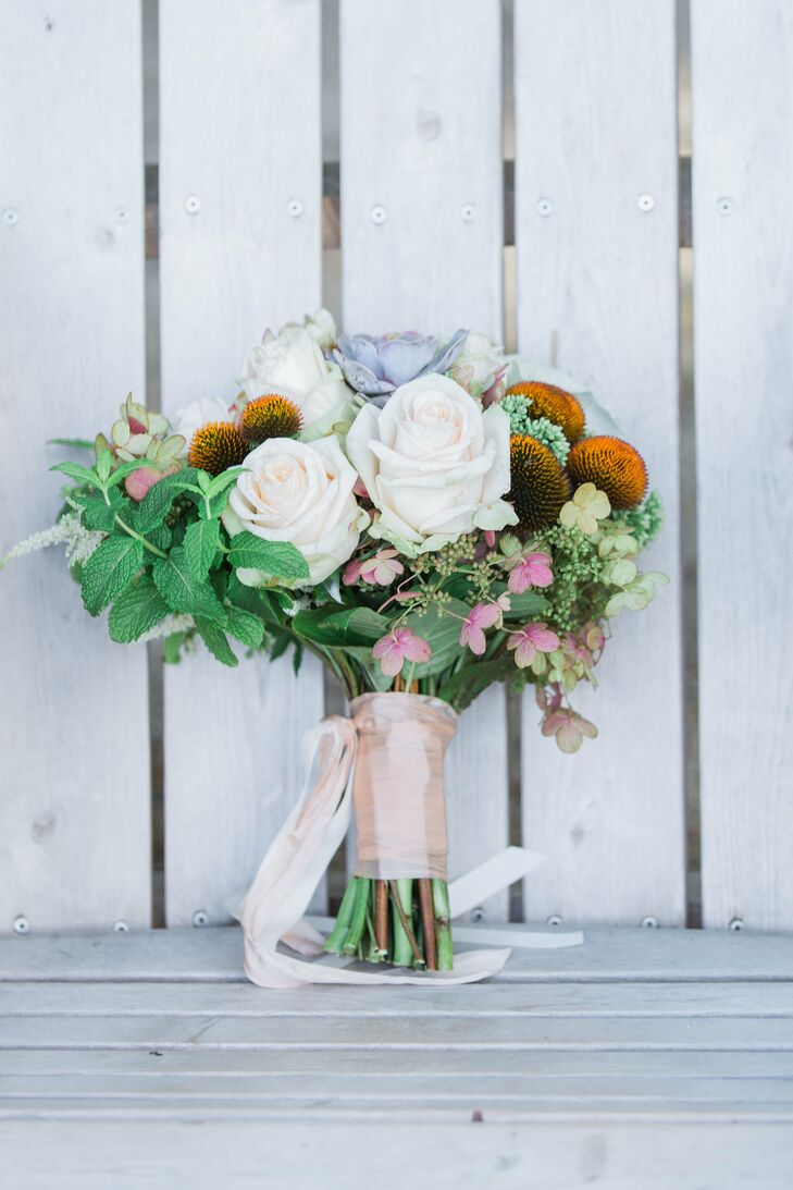 With Chrissy and Mike's rustic theme in mind, Cymbidium Floral created a textured arrangement of roses, wildflowers, hydrangeas, mint and more for Chrissy to carry down the aisle.