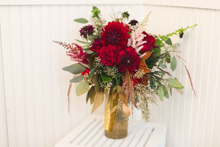 The bridesmaids carried bouquets of rich red roses and dahlias accented by eucalyptus and astilbe.